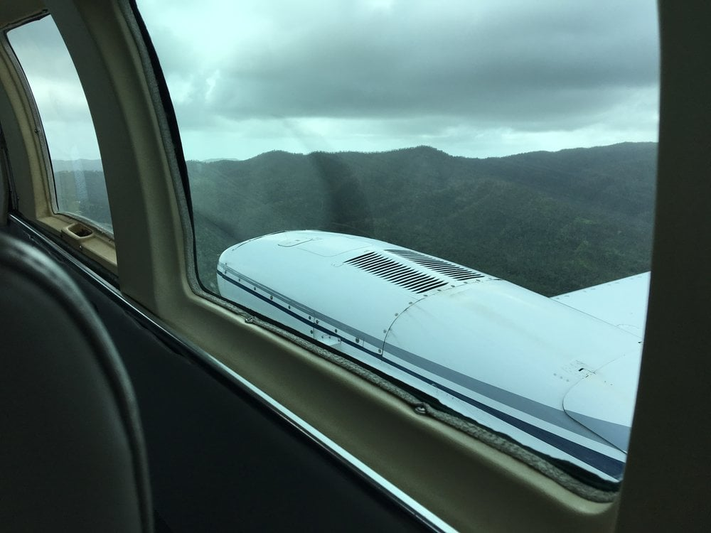 Window of small plane with mountains ahead