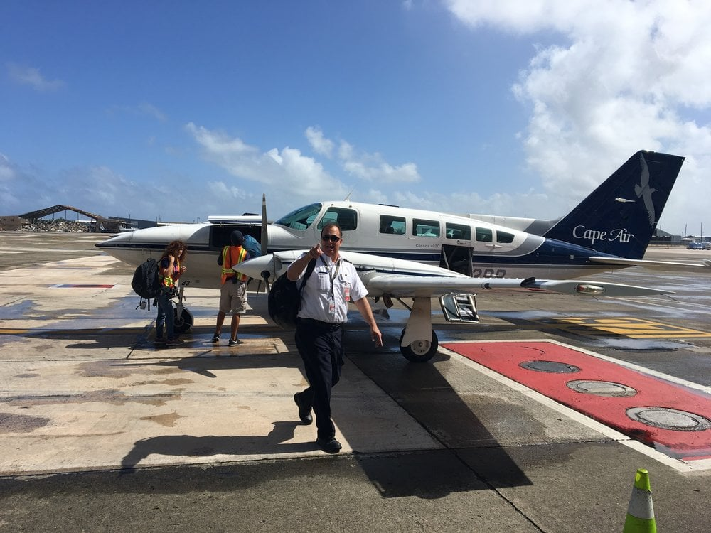 Small plane on tarmac with captain foreground pointing at the camera