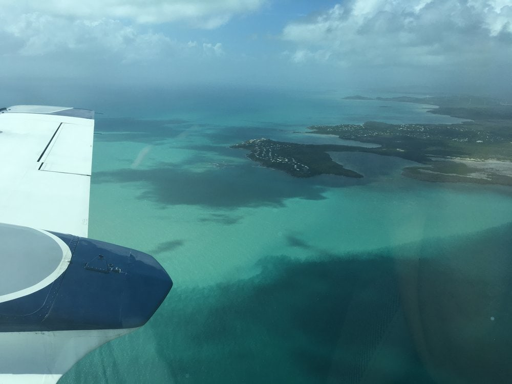 View of small plane wing and water and coastline below