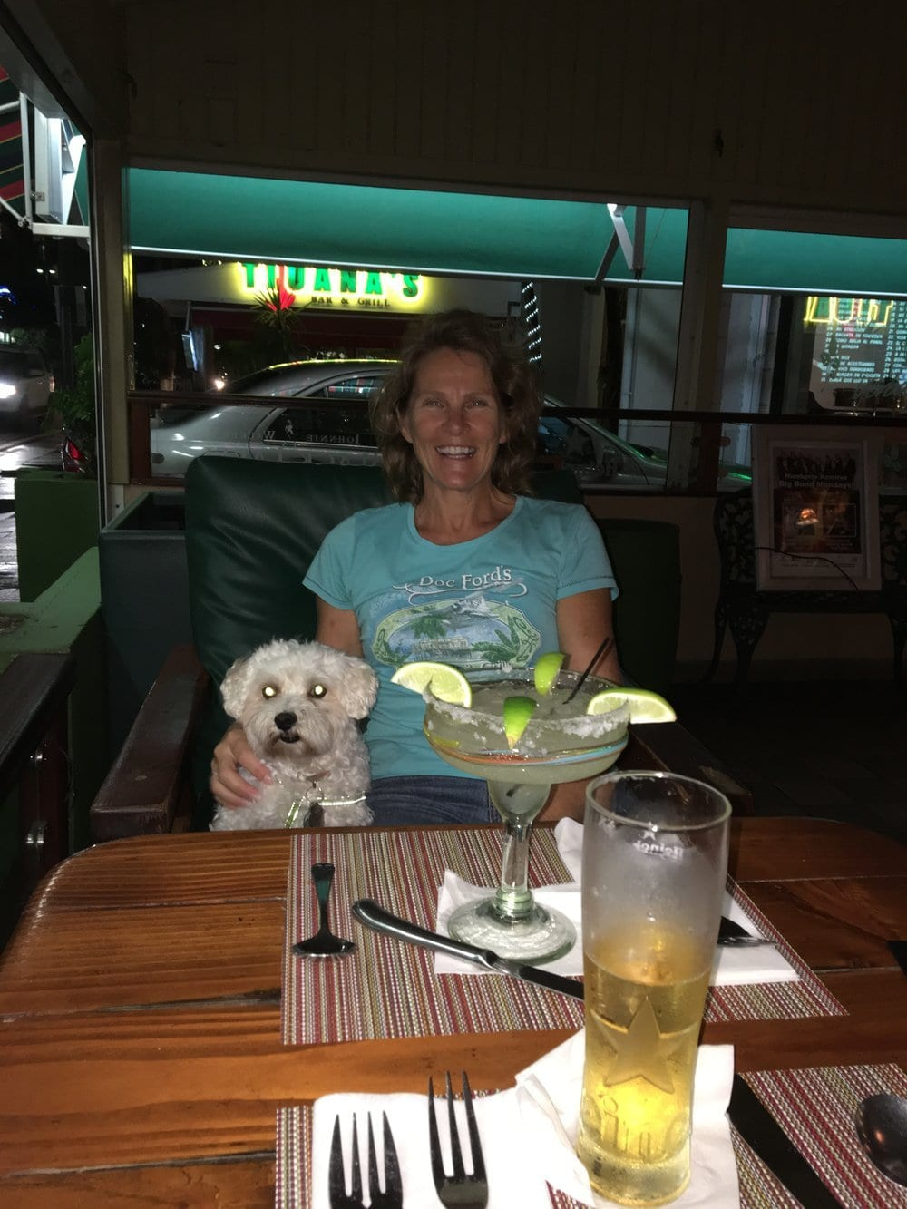 Deb and Maxwell the dog at a table with a margarita and beer