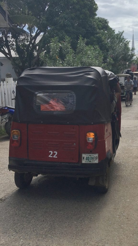 Three wheel tuk-tuk taxi driving down the road